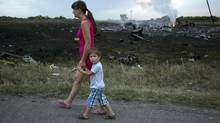 A woman with a child walks past the crash site of a passenger plane near the village of Grabovo, Ukraine. Ukraine said a passenger plane carrying 295 people was shot down Thursday as it flew over the country, and both the government and the pro-Russia separatists fighting in the region denied any responsibility for downing the plane. (Dmitry Lovetsky/AP)