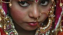 An Indian bride wears gold ornaments on her wedding day in New Delhi. Taxes may rise, but gold is the investment of choice in India. (ADNAN ABIDI/REUTERS)