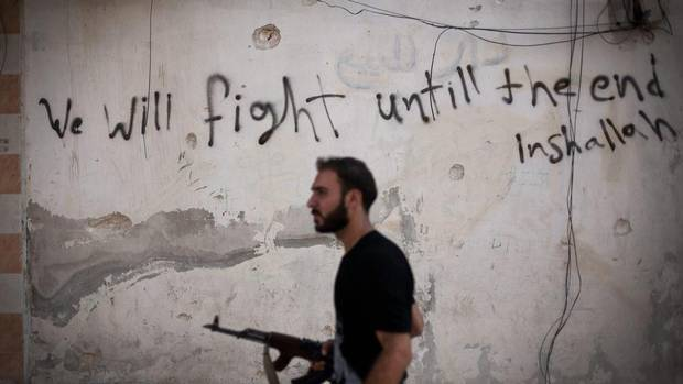 An FSA soldier walks through a street in Amariya district in Aleppo, Syria. Syria's most prominent defector said in an interview that aired Monday that he opposes any foreign military intervention in the country's civil war and that he is confident the opposition can topple President Bashar Assad's regime. But Manaf Tlass, a Syrian general who was the first member of Assad's inner circle to join the opposition, said the rebels need weapons. (Manu Brabo/AP)