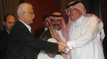 Syrian National Council member George Sabra (L) shakes hands with member of the Syrian opposition Salem Al Mslat in Doha November 9, 2012. (MOHAMMED DABBOUS/REUTERS)