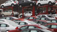 Newly built cars sit in a shipping lot near GM's assembly plant in Oshawa, Ont. General Motors says it expects to close one of the two lines at the plant by June 1, 2013. (Reuters)