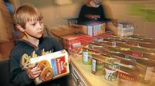 Brothers Adam, 7 (left) and J.J., 10, run food boxes and cans around the kitchen as part of the game Set Up Shop from the book Sneaky Fitness: Fun, Foolproof Ways to Slip Fitness Into Your Child's Everyday Life. (J.P. Moczulski/The Globe and Mail)
