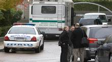 Investigators stand outside the scene of a multiple homicide in Surrey, B.C., on Oct. 21, 2007. (Jonathan Hayward/The Canadian Press)