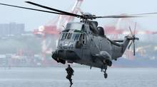 A Canadian soldiers jumps into Halifax harbour from a Sea King helicopter as he participates in advanced amphibious training from the Shearwater Jetty in Halifax on Tuesday, July 30, 2013. (Andrew Vaughan/THE CANADIAN PRESS)