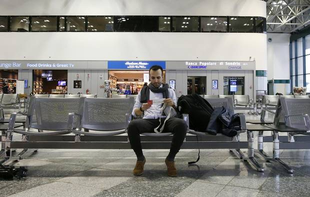 Iranian-born bioengineer researcher Nima Enayati looks at his boarding pass as he waits at Milan's Malpensa international airport in Italy on Sunday afternoon, hours after a U.S. appeals court blocked an attempt to re-impose the immigration ban.