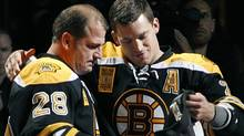 Retired Boston Bruins' Mark Recchi (28) receives the coveted team jacket from Andrew Ference prior to their NHL hockey season-opening game against the Philadelphia Flyers in Boston Thursday, Oct. 6, 2011. (AP Photo/Elise Amendola) (Elise Amendola/AP)