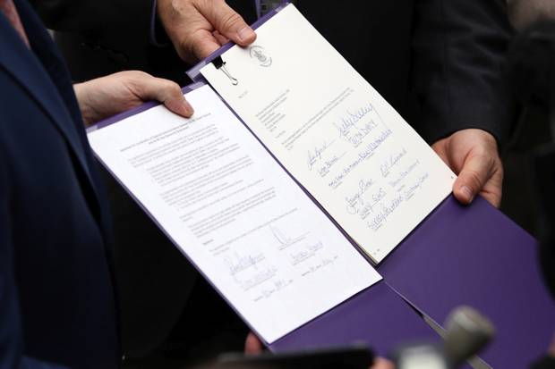 B.C. NDP leader John Horgan and B.C. Green Party Leader Andrew Weaver hold a signed document in which they agree to take down the Liberal government and support an NDP minority government.