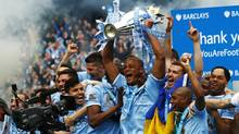 Manchester City's captain Vincent Kompany (C) celebrates with the English Premier League trophy following their soccer match against West Ham United at the Etihad Stadium in Manchester, northern England May 11, 2014. (DARREN STAPLES/REUTERS)