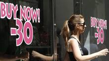 A woman comes out of a shop with discount signs in central Athens. (JOHN KOLESIDIS/JOHN KOLESIDIS/REUTERS)