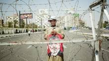 A supporter of Mohammed Morsi demonstrates near an army roadblock in the Nasr City neighborhood of Cairo, July 4, 2013. As Egyptians contemplated a new and uncertain political landscape after the military ouster of Mohammed Morsi as president, the country's partners, neighbors and supporters seemed divided in their response on Thursday. (YUSUF SAYMAN/NYT)