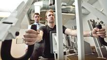 Trainer Blair Wilson monitors Ian Hodgins while he uses a seated row machine during a one-on-one circuit training session at MedX Precision Fitness in Toronto on December 23, 2010. (Jennifer Roberts for the Globe and Mail/Jennifer Roberts for the Globe and Mail)