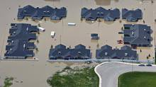 A group of houses are surrounded in flood water in High River, Alberta, south of Calgary June 23, 2013. (ANDY CLARK/REUTERS)
