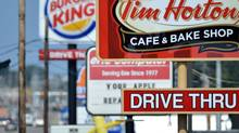 Signs for a Tim Hortons restaurant, foreground, and a Burger King restaurant are displayed along Peach Street Tuesday, Aug. 26, 2014, in Erie, Penn. (Christopher Millette/AP)