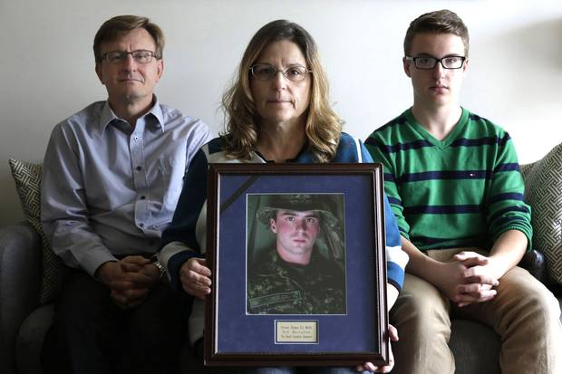 Anita Cenerini holds a portrait of her son, Private Thomas Welch, at her Winnipeg home in October, 2016, with Pte. Welch's stepfather, Grant Palmer, and brother, Jacob Cenerini-Palmer. In 2004, Pte. Welch, suffering from post-traumatic stress disorder, died by suicide three months after returning from Afghanistan.