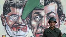 A soldier stands in front of a mural depicting Egypt's former President Hosni Mubarak (R), former Field Marshal Mohamed Hussein Tantawi (C) and Egypt's President Mohamed Mursi drawn on the wall of the presidential palace in Cairo December 12, 2012. (Khaled Abdullah/REUTERS)