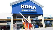 A man carries building supplies from a Rona store in Toronto on July 31, 2012. (Nathan Denette/THE CANADIAN PRESS)