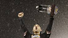 San Francisco Giants second baseman Marco Scutaro (19) celebrates in the rain with his MVP trophy (David J. Phillip/Reuters)