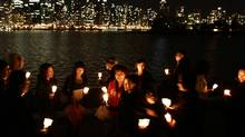 A group of friends hold candles as they gather along the Stanley Park seawall to mark Earth Hour in Vancouver, B.C., on Saturday March 27, 2010 to bring awareness to climate change. (Darryl Dyck/ The Canadian Press/Darryl Dyck/ The Canadian Press)