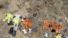 Rescue workers and miners dry clothes as they help with rescue operations of the nine trapped miners at Cabeza de Negro gold-and-copper mine, near the mine in Ica April 10, 2012. (MARIANA BAZO/REUTERS/MARIANA BAZO/REUTERS)
