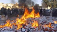 Fighters from Islamic State in Iraq and the Levant (ISIL) burn confiscated cigarettes in the city of Raqqa April 2, 2014. (STRINGER/REUTERS)