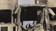 Palestinian youths inspect a damaged building after it was hit by an Israeli airstrike in Beit Lahiya, northern Gaza Strip, Tuesday, July 15, 2014. (Adel Hana/AP)