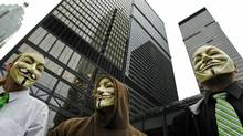 Masked protesters with the Occupy movement gather at the heart of Toronto's financial district on Oct. 15, 2011. (Peter Power/Peter Power/The Globe and Mail)