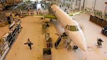 Embraer's employees at the company's factory in Sao Jose dos Campos, Brazil: the company is contemplating launching a new jet in the same category as rival Bombardier Inc.?s C Series long-range plane. (Victor R. Caivano/AP)