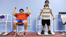 Weighing in at 68kg , Prashant Kumar, left, age 8, works on an exercise machine on Nov. 29, 2006 with his brother Prakeet, who comes to the gym with Prashant for support, at the Youth Visions Fitness Center in Upper Marlboro, Maryland. (TIM SLOAN/TIM SLOAN/AFP/Getty Images)