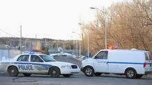 Police vehicles block the road leading to a detention centre in St. Jerome, Que., Sunday, March 17, 2013, where two prisoners made a daring escape by helicopter. (GRAHAM HUGHES/THE CANADIAN PRESS)