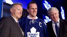 Newly-named Toronto Maple Leafs captain Dion Phaneuf, centre, poses with Maple Leafs coach Ron Wilson, left, and President and GM Brian Burke during a press conference to make the announcement in Toronto Monday, June 14, 2010. (Darren Calabrese/THE CANADIAN PRESS)