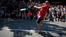 Canadian Olympic alpine skier Mike Janyk of Vancouver tosses a Frisbee while marching in the Vancouver Pride Parade on August 4, 2013. (Darryl Dyck/The Canadian Press)