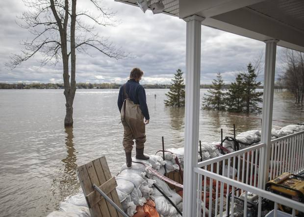 Patrice Pepin walks along a barrier of sandbags holding back the Ottawa River's waters at the home of his brother Christian Pepin and wife Marie-Pierre Chalifoux on Fournier street in the municipality of Saint-Andre-d'Argenteuil, on May 9, 2017.
