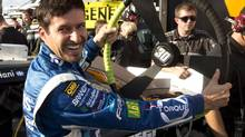 Alex Tagliani laughs at the giant steering wheel his crew put in his car before he went out and won the pole for the NAPA Auto Parts 200 NASCAR Nationwide race Friday, August 17, 2012 at the Circuit Gilles Villeneuve in Montreal. (Ryan Remiorz/THE CANADIAN PRESS)