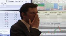An employee stands near an information screen at the MICEX stock exchange in Moscow, June 1, 2012 (SERGEI KARPUKHIN)