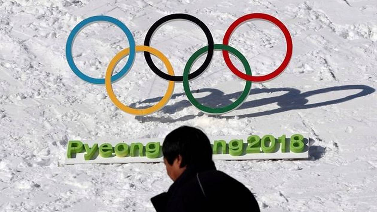 A man walks by the Olympic rings in Pyeongchang.