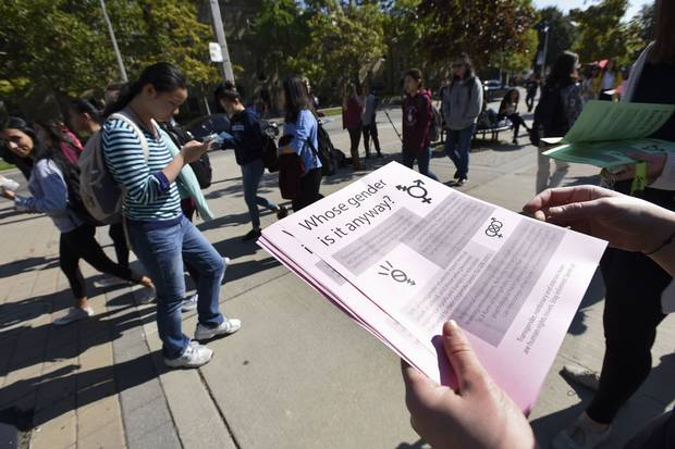 Oct. 5, 2016: A volunteer hands out a leaflet explaining gender issues and language at a rally outside the University of Toronto's Sidney Smith Hall over the Jordan Peterson controversy.
