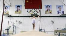 A young gymnast practices on the balance beam under a Chinese national flag and the Olympic rings during a training session at a juvenile gymnastics training base in Wuhan, Hubei province July 13, 2012. (DARLEY SHEN/REUTERS)