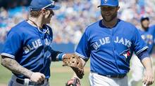 Toronto Blue Jays starting pitcher Mark Buehrle laughs with Blue Jays Brett Lawrie, left, while walking back to the dugout against Kansas City Royals during eighth inning AL baseball action in Toronto on Sunday, June 1, 2014. (Nathan Denette/THE CANADIAN PRESS)