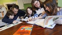 WINNIPEG, MANITOBA - September 25, 2013 - Jim and Andrea Kavanagh work with their children Eric, 5, Charlotte,10, and Carolyn, 12, on French homework in their Winnipeg home recently. Friday, January 25, 2013. Andrea Kavanagh went to French Immersion and eventually became a French elementary teacher. There is a rise in French Immersion enrolment and its potential link to the first kids of French Immersion having their own kids in school now. (John Woods for the Globe and Mail) (JOHN WOODS/GLOBE AND MAIL)