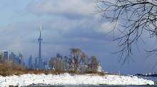 The Toronto skyline is seen beyond the ice buildup at Humber Bay park as Lake Ontario's water freezes on contact as it splashes ashore. (Peter Power/The Globe and Mail)
