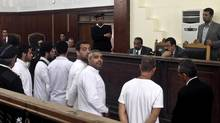 Al-Jazeera English bureau chief Mohamed Fahmy, center, producer Baher Mohamed, center left, and correspondent Peter Greste, second right, stand in a courtroom along with several other defendants, in Cairo, Egypt, Monday, March 31, 2014. (Sarah El Deeb/AP)