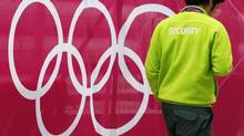 A security guard passes Olympic Rings signage at the London 2012 Olympic Park in Stratford, east London July 17, 2012. (LUKE MACGREGOR/Reuters)