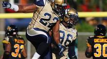 Winnipeg Blue Bombers Terrell Parker, left, celebrates with teammate Alex Hall during first quarter CFL action in Guelph, Ont., Saturday, July 13, 2013. Later in the game, Parker suffered a torn knee ligament that will keep him out of the lineup for the rest of the season. (Aaron Lynett/THE CANADIAN PRESS)