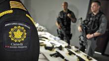 Police officers and Canadian Border Services agents display a seized cache of guns and illegal drugs in Brampton, Ont., on May 21, 2007. (Fred Lum/Fred Lum/The Globe and Mail)