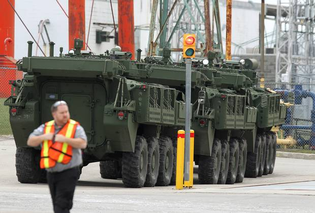 A security guard walks in front of three LAVs parked on the lot of the General Dynamics factory in London, Ont.
