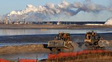 Workers use heavy machinery in the tailings pond at the Syncrude oil sands extraction facility near the town of Fort McMurray in Alberta Province, Canada on October 25, 2009. (MARK RALSTON)