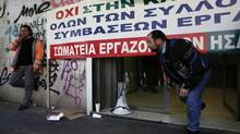 Employees of the Athens-Piraeus Electric Railway block the entrance of the company headquarters in Athens Dec. 19, 2012. Greek public sector workers walked off the job on Wednesday in protest at new austerity measures and planned layoffs, disrupting local transport, grounding flights and shutting schools and tax offices. (YORGOS KARAHALIS/REUTERS)