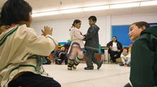 Grade three students Harry Kango, right, and Beatrice Kunnk, left, watch classmates Mikijuk Arnaquq, back left, and Elisapee Michael, back right, rehearse a traditional Inuktitut dance at the Nakasuk Elementary School in Iqaluit, Nunavut on Tuesday, March 31, 2009. (NATHAN DENETTE)