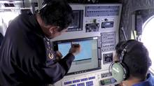 In this photo released by Malaysian Maritime Enforcement Agency, Director General of the Malaysian Maritime Enforcement Agency Admiral Mohd Amdan Kurish, left, checks a radar during a searching for the missing Malaysia Airlines plane off Tok Bali Beach in Kelantan, Malaysia. (AP Photo/Malaysian Maritime Enforcement Agency)