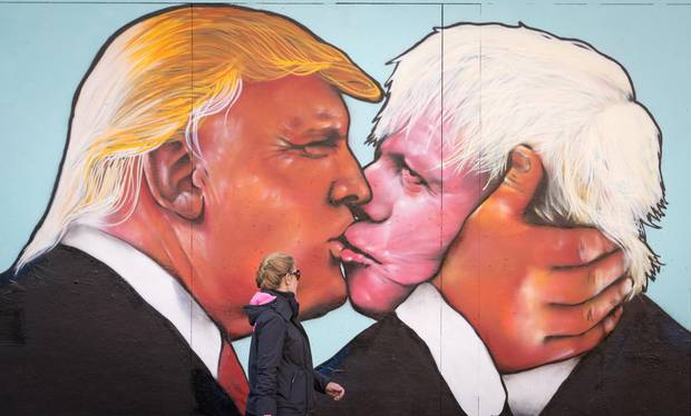 A woman passes a mural on a derelict building in Stokes Croft showing U.S. presidential hopeful Donald Trump sharing a kiss with former London mayor Boris Johnson on May 24, 2016, in Bristol, England.